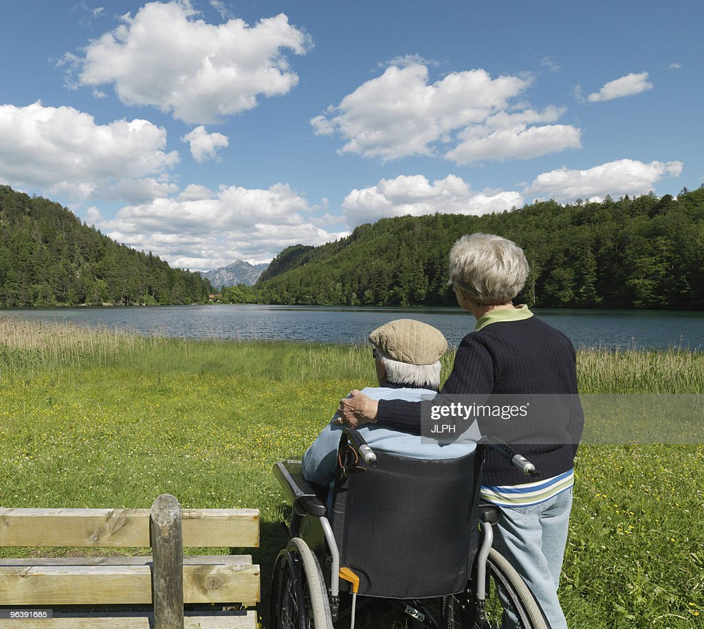Senior couple relaxing by lake : Stock Photo
