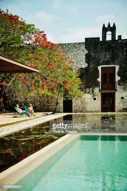 Senior couple relaxing by pool in courtyard of luxury tropical resort