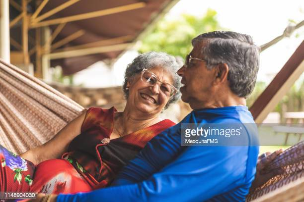 pares sênior que relaxam em um hammock - homens idosos - fotografias e filmes do acervo