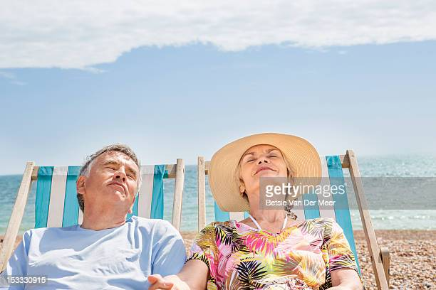 senior couple relaxing in deckchairs on beach.