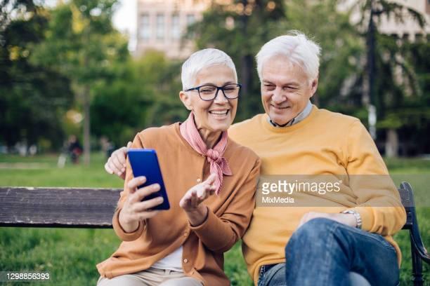 coppia senior che si rilassa nel parco e naviga in rete - 55 59 anni foto e immagini stock