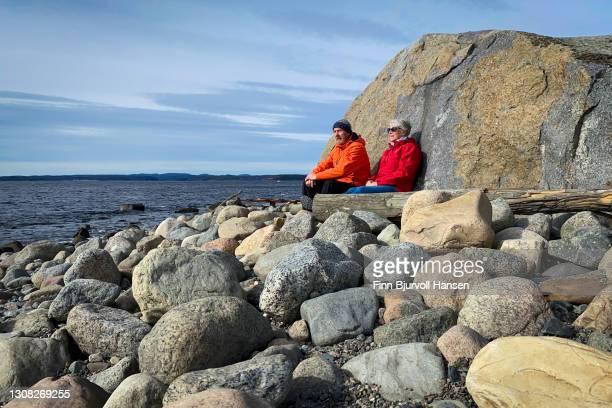 senior couple relaxing in the sun at the stony beach of molen in vestfold norway - finn bjurvoll stock-fotos und bilder