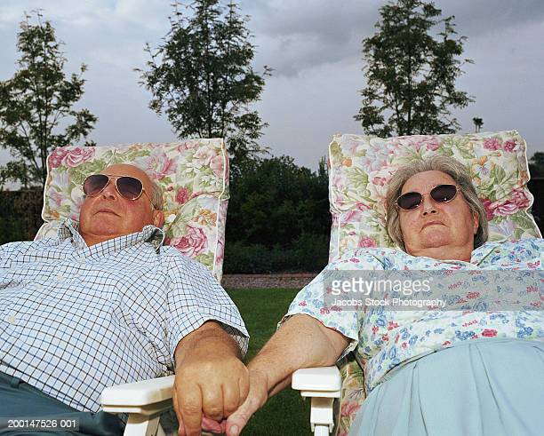Senior couple relaxing on garden chairs holding hands