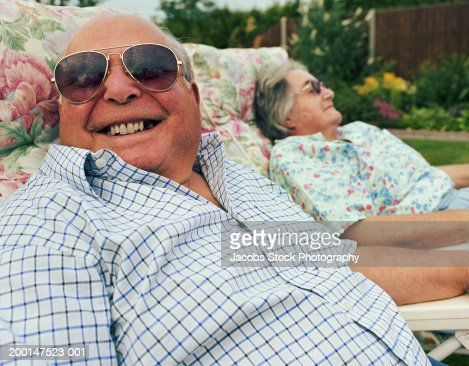 Senior couple relaxing on garden chairs (focus on man in foreground)