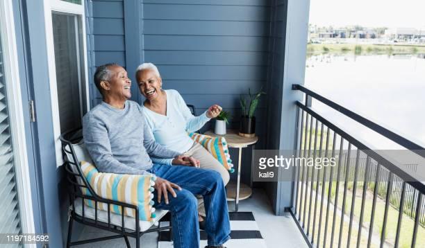 coppia anziana rilassante sotto il portico, tenendosi per mano, ridendo - coppia anziana foto e immagini stock