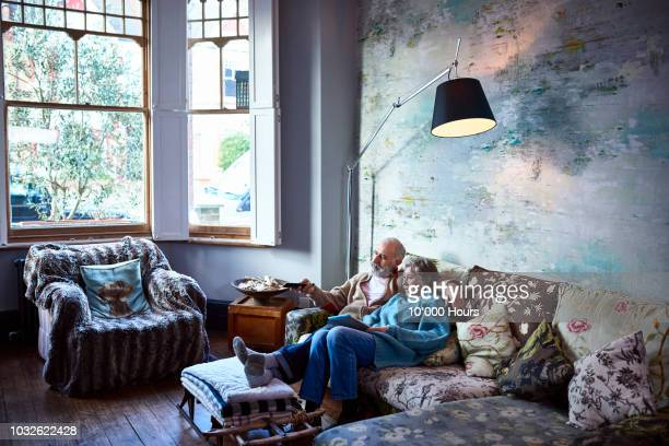Senior couple relaxing on sofa in boho living room watching tv