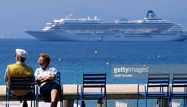 Senior couple relaxing on the Promenade de la Croisette stretching about 2 km long along the shore of the Mediterranean Sea