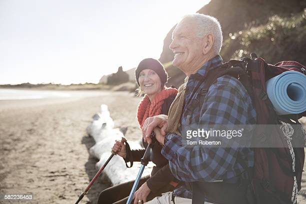 Senior couple resting on beach during hike
