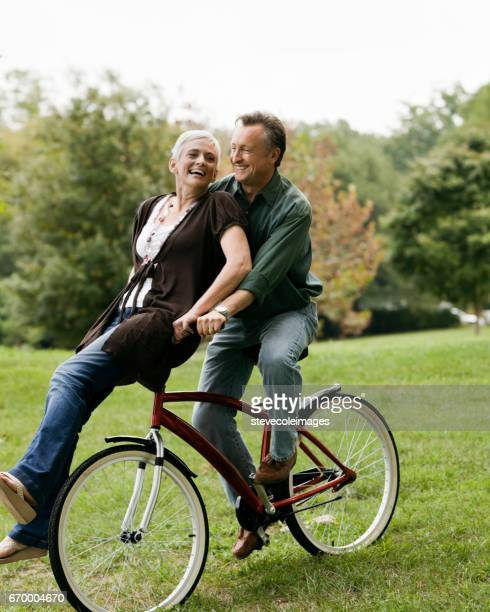 senior couple riding bicycle - handlebar stock photos and pictures