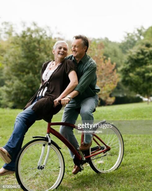 bicicleta de equitação do casal sênior - guidom - fotografias e filmes do acervo