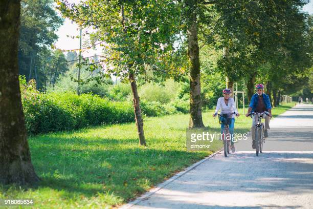senior couple riding bicycle - long sleeved stock pictures, royalty-free photos & images