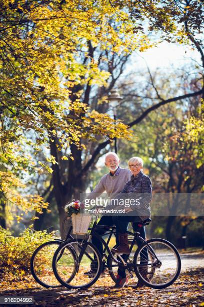 Senior couple riding bicycles in the park