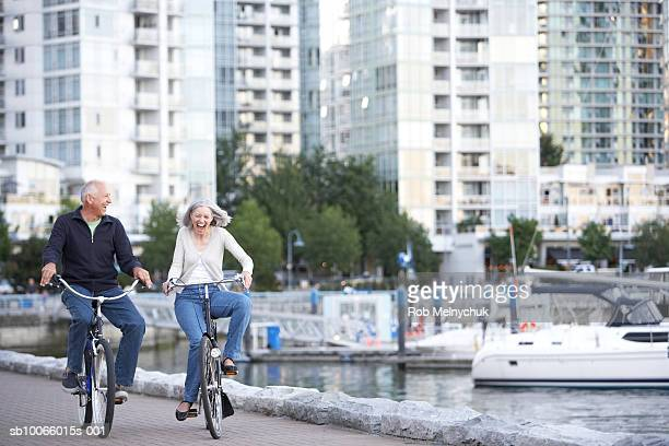 senior couple riding bikes along seawall - seawall stock pictures, royalty-free photos & images