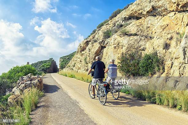 senior couple riding in electrical bicycles - castellon de la plana stock pictures, royalty-free photos & images
