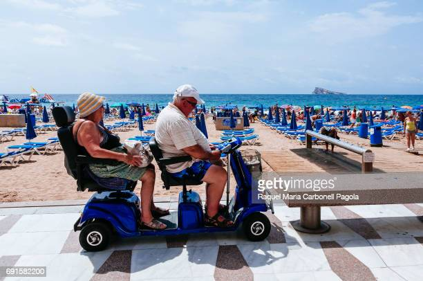 Senior couple riding mobility scooter on Levante beach promenade