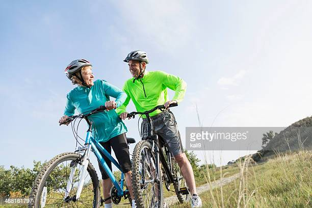 Senior couple riding mountain bikes