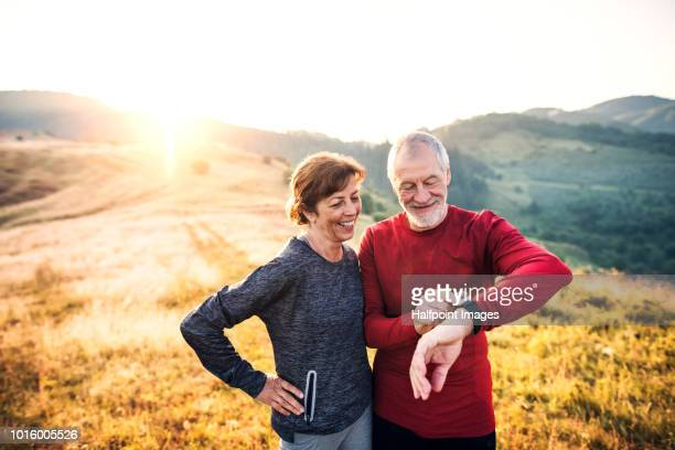 senior couple runners resting outdoors in nature at sunrise, using smart watch. - smart watch stock pictures, royalty-free photos & images