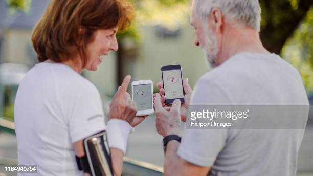 a senior couple runners with smartphone standing outdoors, talking. - checking sports stock pictures, royalty-free photos & images