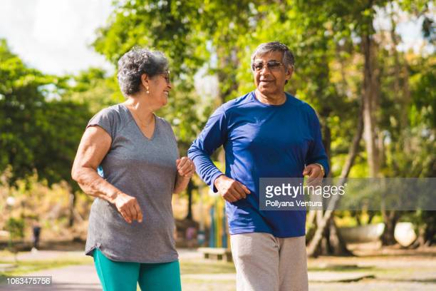 Senior couple running at park