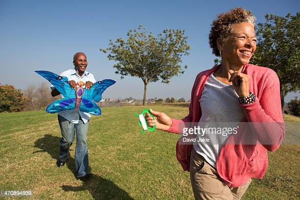 senior couple running in park with kite - kite toy stock photos and pictures