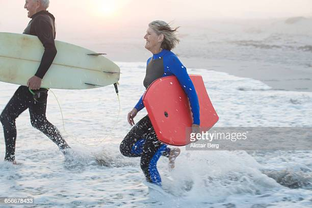 Senior couple running into sea with surf boards