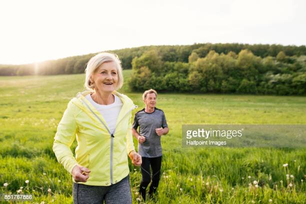 Senior couple running outside on the green hills.