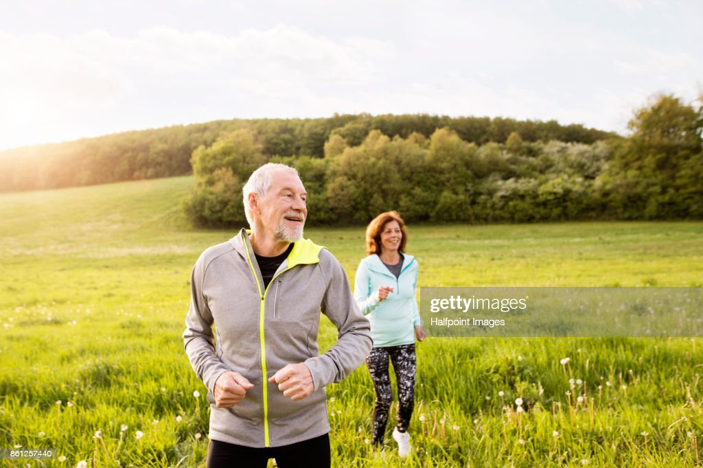 Senior couple running outside on the green hills. : Stock Photo