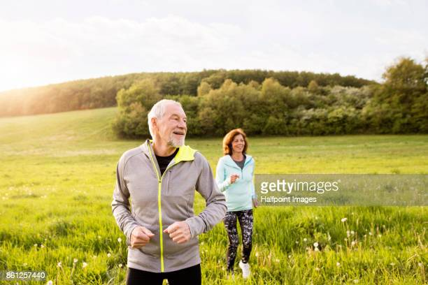 Senior couple running outside on the green hills.