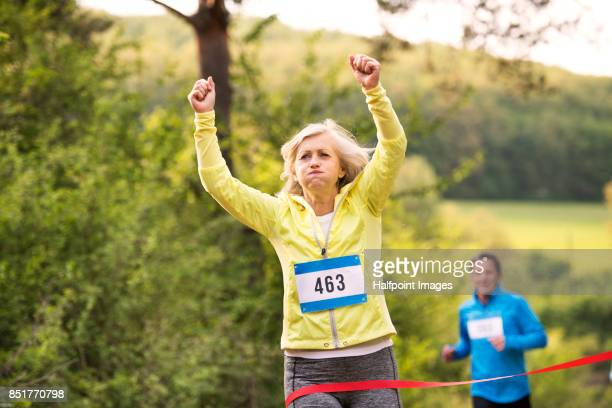 Senior couple running race in nature on dirt road.