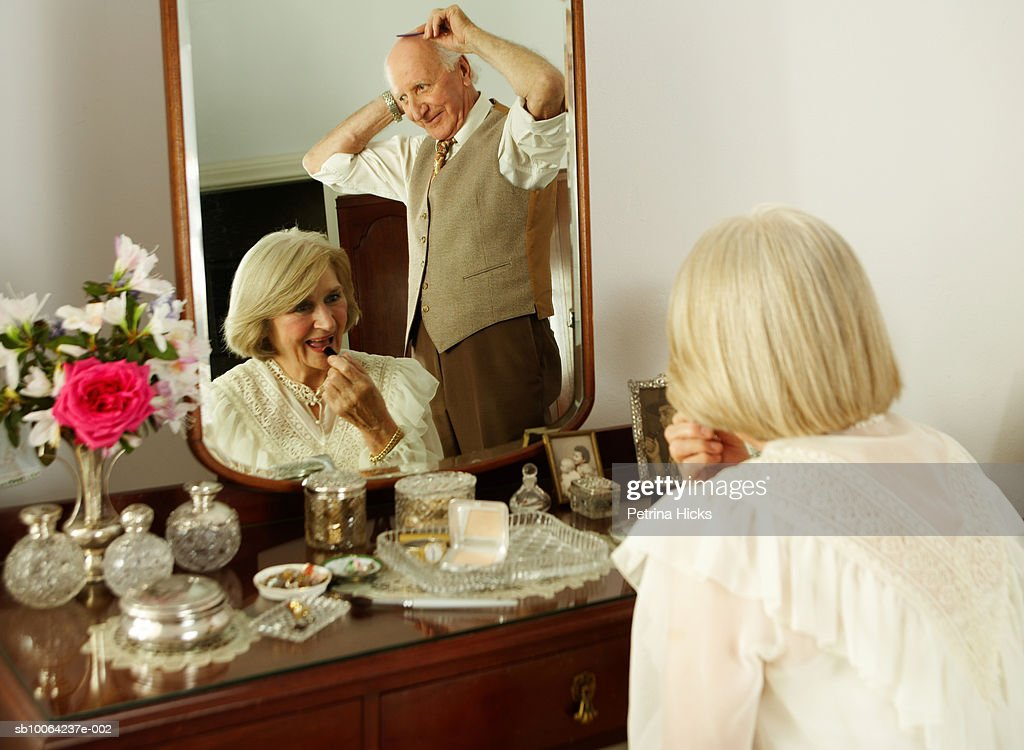 Senior couple seen in mirror of dressing table : Stock Photo