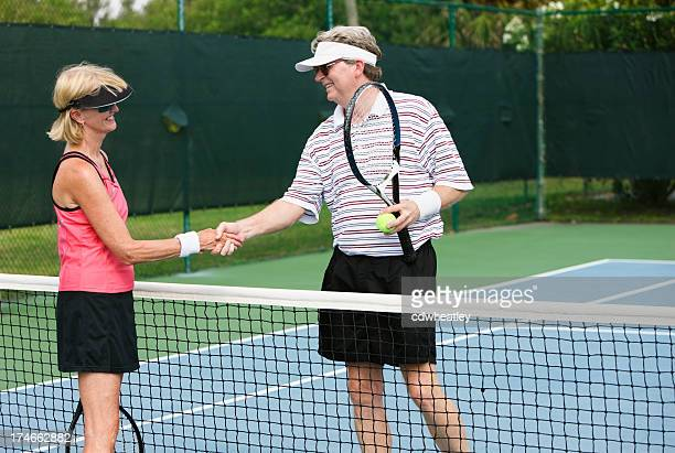 senior couple shaking hands after tennis match - racquet sport stock photos and pictures
