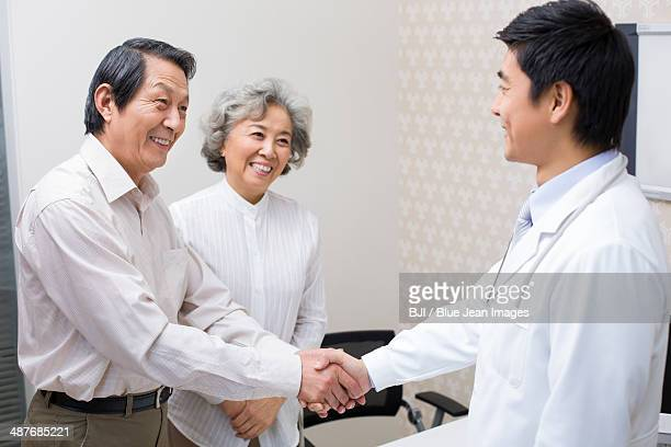 Senior couple shaking hands with doctor in hospital