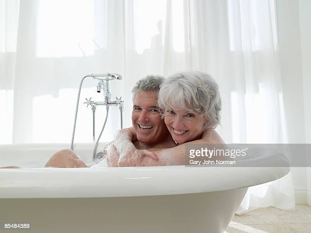 Senior couple share bath together laughing