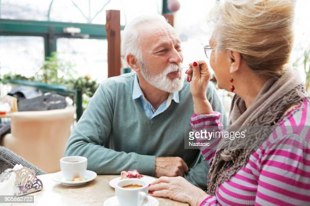 senior couple sharing cake - sweet food stock pictures, royalty-free photos & images