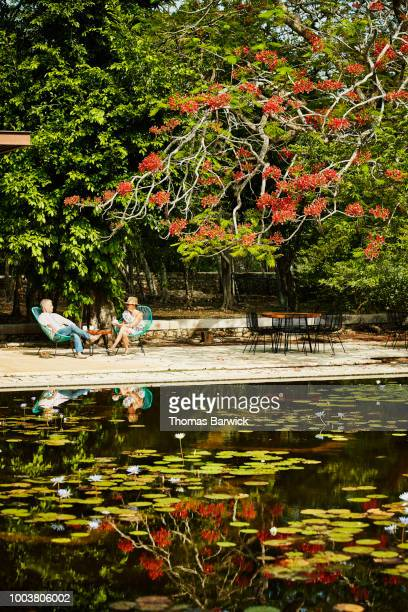Senior couple sharing coffee while sitting in courtyard of luxury resort