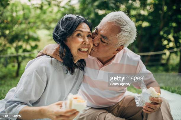 senior couple sharing love on picnic in park - husband stock pictures, royalty-free photos & images