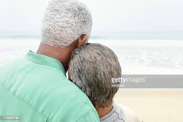 senior couple sharing quiet moment on beach - real wife sharing stock photos and pictures