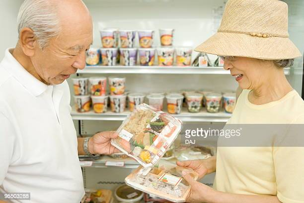 senior couple shopping at convenience store - convenience store stock photos and pictures
