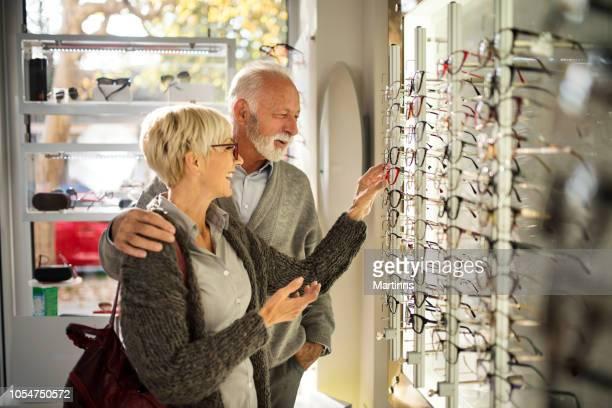 senior paar winkelen voor brillen - bril brillen en lenzen stockfoto's en -beelden