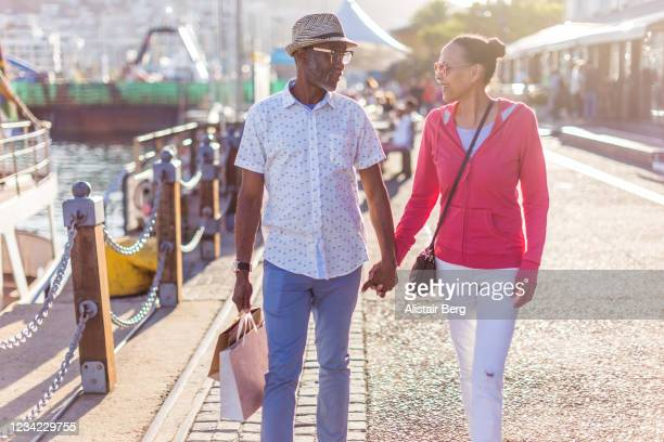 senior couple shopping in cape town waterfront - uferviertel stock-fotos und bilder