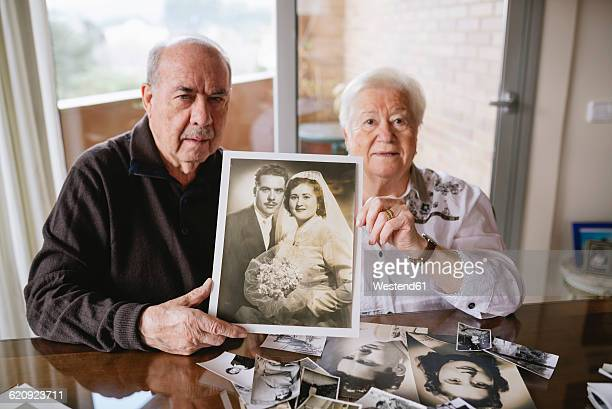 Senior couple showing their wedding photo at home
