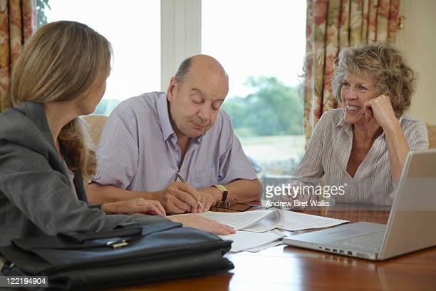 senior couple signing documents with adviser