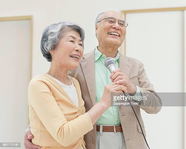 Senior Couple Singing Holding Microphone