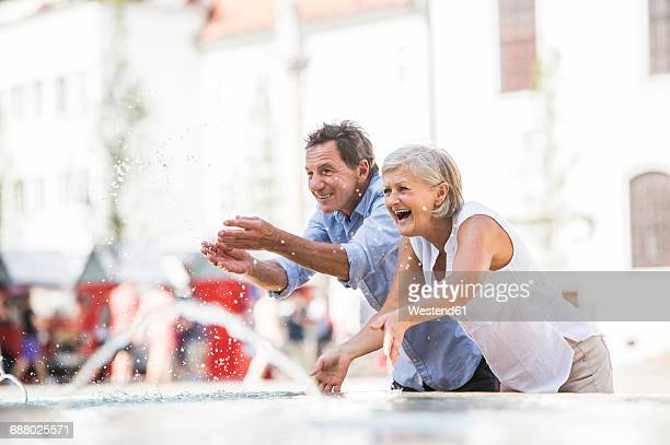 senior couple siplashing with water of a fountain - older woman bending over stock pictures, royalty-free photos & images
