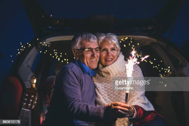 Senior couple sit in open car trunk and hold spark sticks in their hands