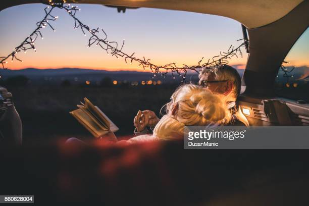 Senior couple sit in open car trunk and reading a book