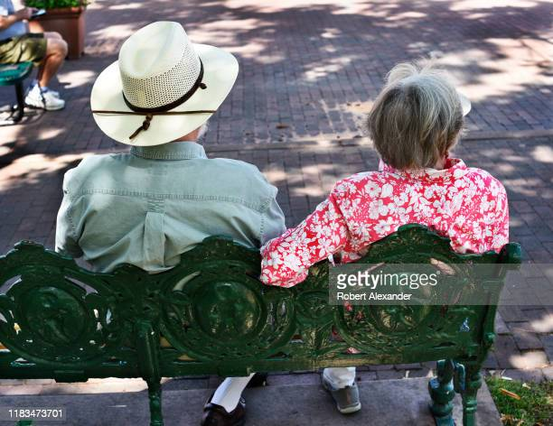 A senior couple sit on a park bench in Santa Fe New Mexico