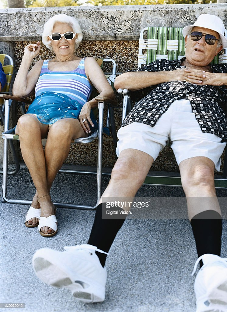 Senior Couple Sit on Chairs Sunbathing : Stock Photo