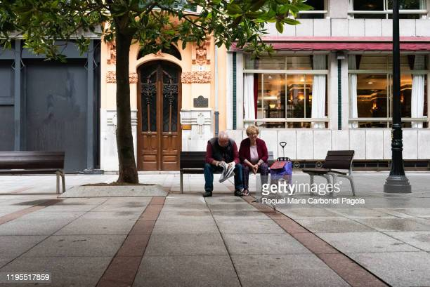 Senior couple sit on city bench alone while looking at a seagull