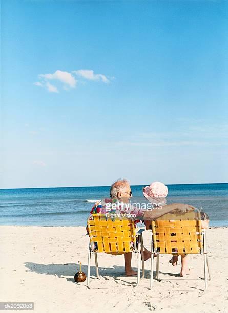 Senior Couple Sit on Deckchairs on the Beach, Talking